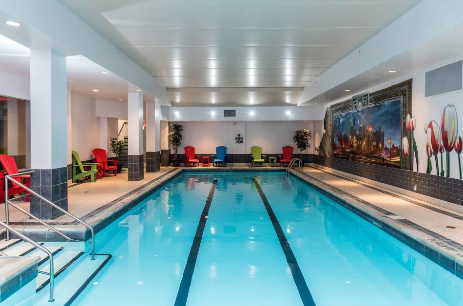 The hotel's indoor lap pool surrounded by chairs and Ottawa paintings