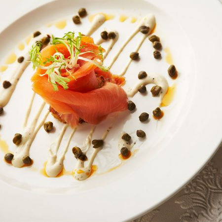 A plate of smoked salmon in a rose shape, garnished with capers and a white sauce, in Grill 41, the Lord Elgin's restaurant.