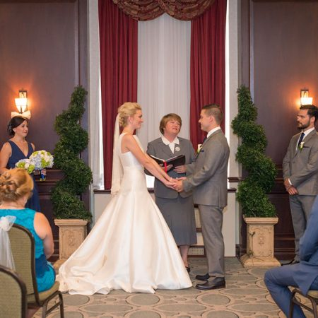Bride and groom holding hands during their wedding ceremony at the Lord Elgin hotel.