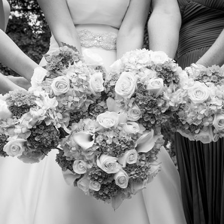 Five wedding bouquets held together by a bride and bridal party at their wedding venue.