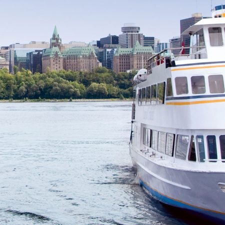 Looking out at Rideau Canal near the Lord Elgin hotel. Views of the city and a white boat.