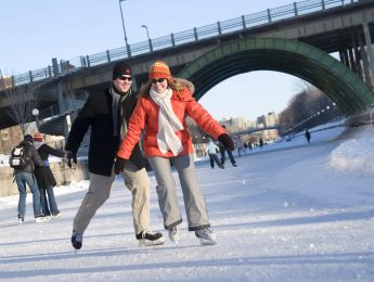 Two people ice skating on the Rideau Canal during Winterlude
